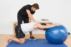 a trainer helps teach physical therapy to a patient on an exercise ball
